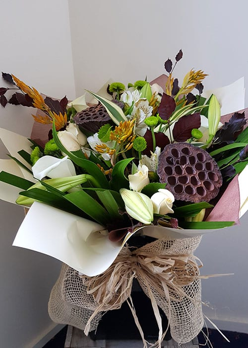 sympathy flower arrangement with New Zealand native fauna and seasonal flowers
